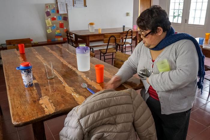 Sandra Cardozo, una usuaria regular del Centro de Dia de la Fundacion IPNA, pone la mesa antes de una comida en el comedor del centro.