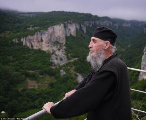 Maxime stands by the church on top of the Katskhi Pillar looking at the beautiful view. He has lived