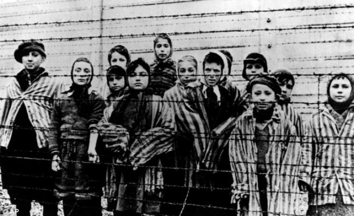 A haunting image of children wearing concentration camp uniforms, taken during the liberation of Aus