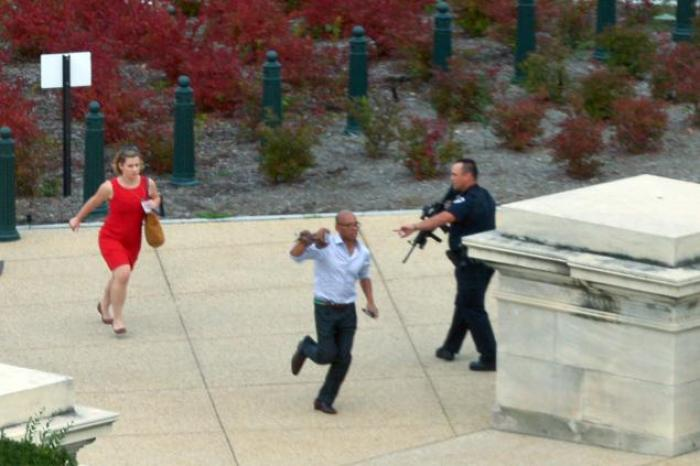 People run for cover at the site of the Capitol Hill shooting October 3.