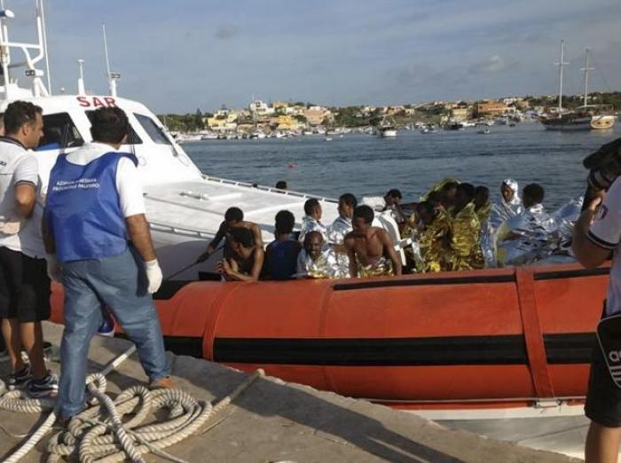 Rescued migrants arrive onboard a coastguard vessel at the Lampedusa harbor.
