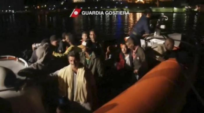 In this image made from video provided by the Italian Coast Guard, survivors of a ship carrying migr