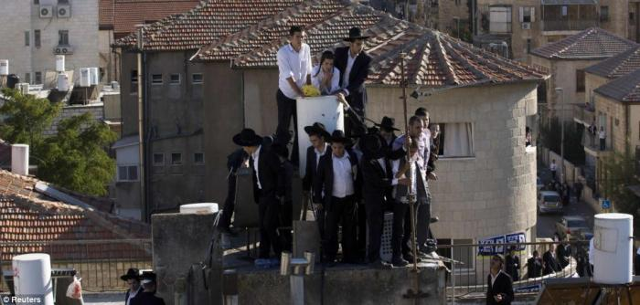 Desperate to glimpse their icon, boys climbed rooftops - the closest they could get as thousands swa