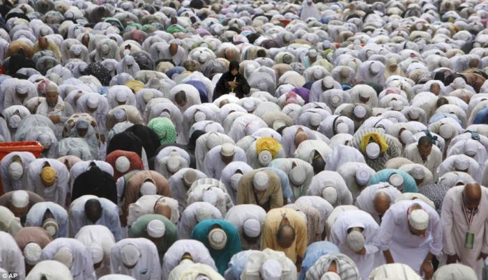 Wearing traditional cloth, people pray on a street near the Grand Mosque, which is the focal point o
