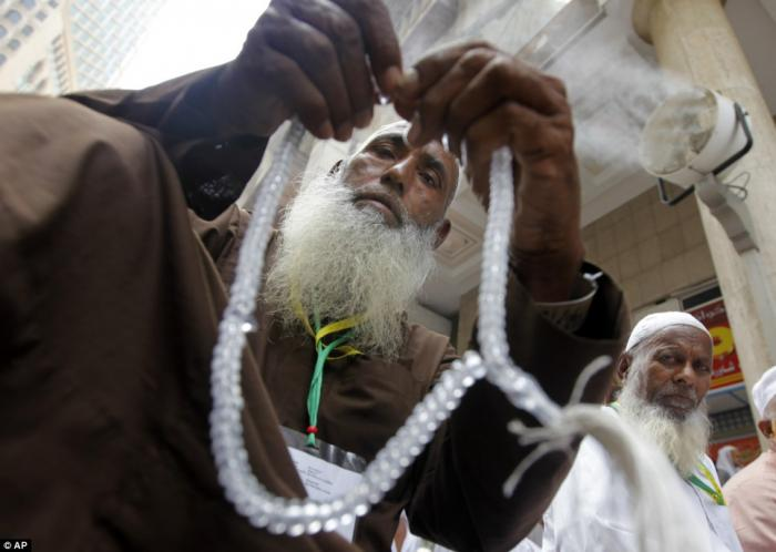 A man with his prayer beads waits for the noon prayers near the Grand Mosque.
