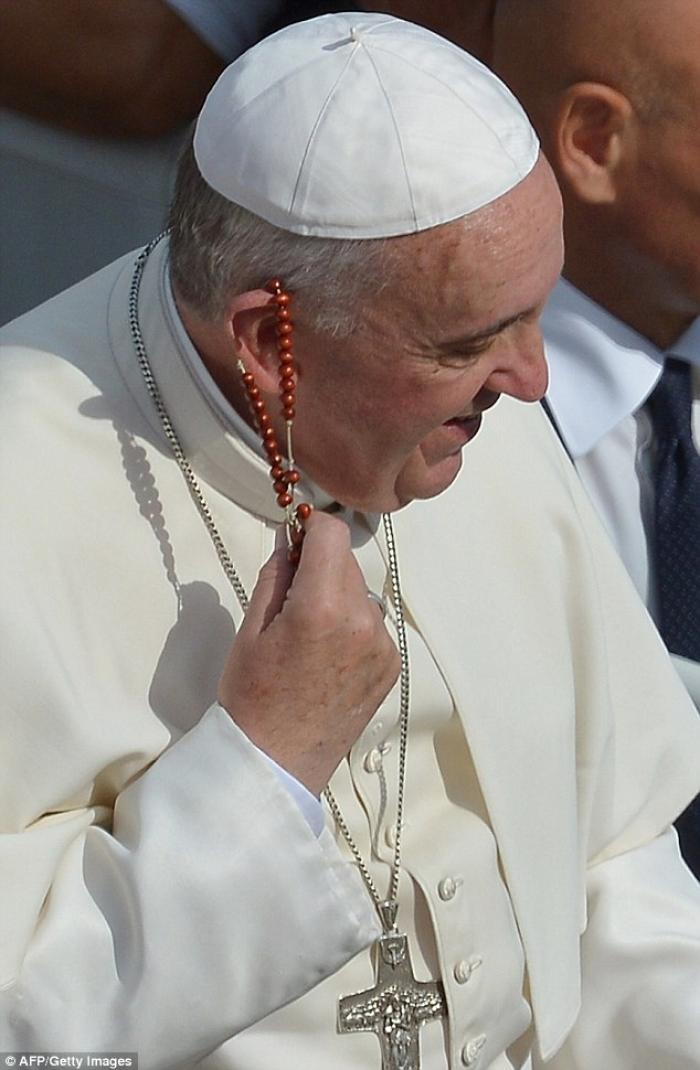 Surprised by the gift, Pope Francis gently removed it from his ear.