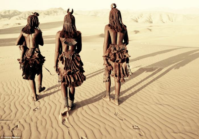 The Himba women walk through the Namib Desert. The Himba wear little clothing, but the women are fam