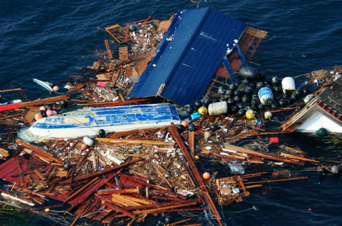 Flotsam from the field reveals entire houses and boats amid the debris.