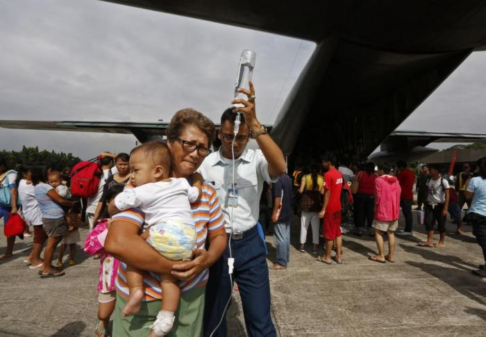 The Philippine Air Force is transporting what people it can. Here, a child on an IV is taken to an a