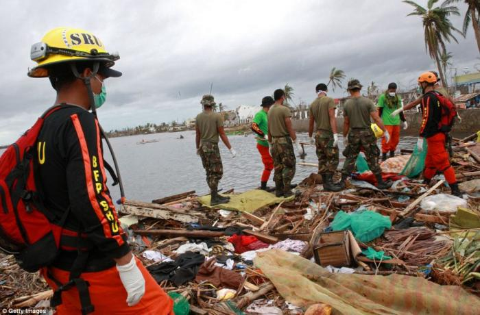 Rescue workers recover bodies from the rubble.