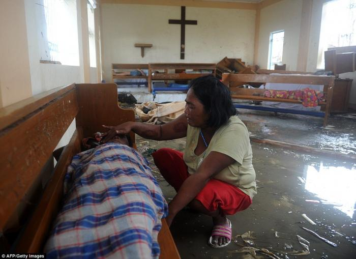 A woman weeps next to the body of her son, killed during the storm.