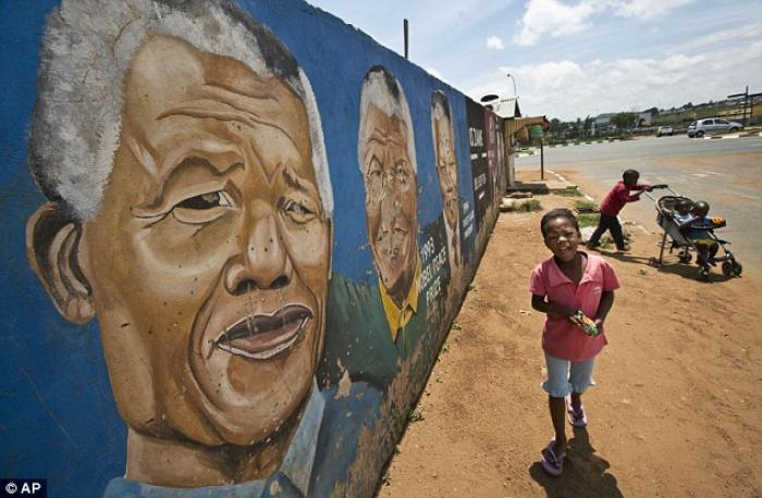 Children walk past a mural depicting Mr Mandela during different stages of his history, on their way