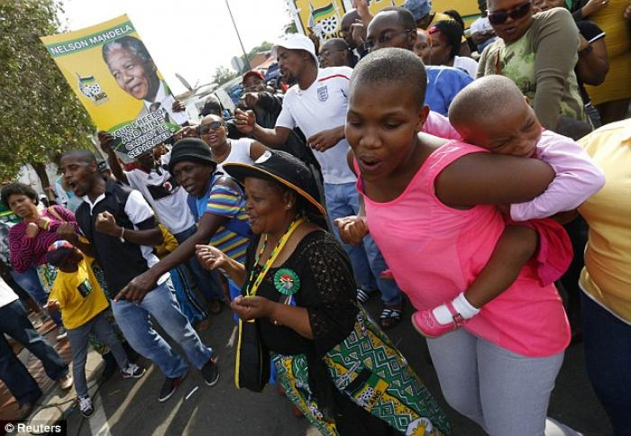 People dance during a gathering of mourners on Vilakazi Street in Soweto, where the former South Afr