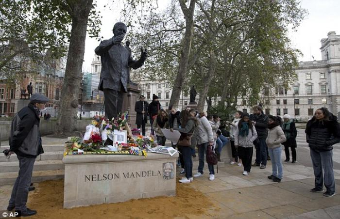 Flowers are laid in tribute at the foot of the Mandela statue in Parliament Square, London.