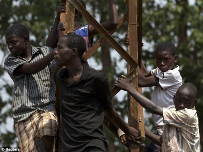 People climb a metal post as they listen to a speech give by the Central African transitional parlia