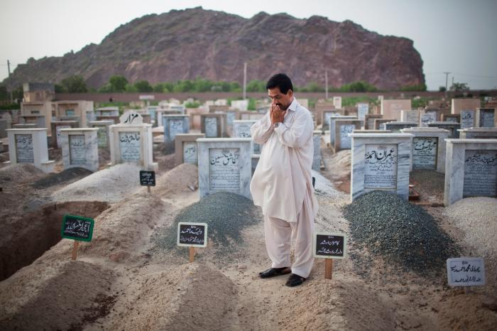 Muhammad Munawar prays at the grave of his slain son, 17-year-old Waleed, in Chenab Nagar, Pakistan.