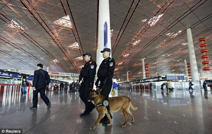 Police patrol with a dog at Beijing International Airport days after the Beijing-bound Malaysian jet