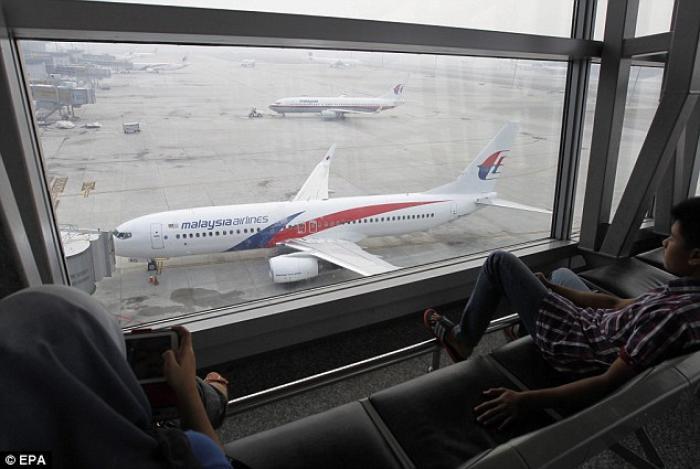 Passengers look at a Malaysian Airline planes at Kuala Lumpur International Airport, Malaysia, on 13