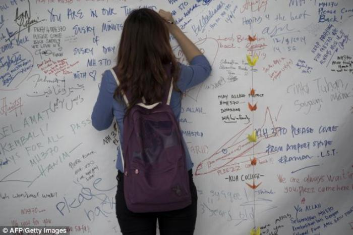 A visitor writes on a banner carrying messages for the passengers of missing Malaysia Airlines fligh