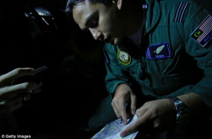 Captain Syukri of the Malaysian Air Forces studies a map during a search and rescue mission flight.