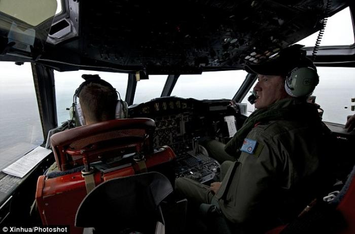 Royal Australian Air Force Flight Engineer Warrant Officer Ron Day keeping watch for any debris or w
