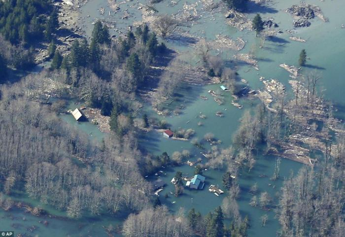 Houses and other structures are shown flooded by the backed-up Stillaguamish River up-river from the