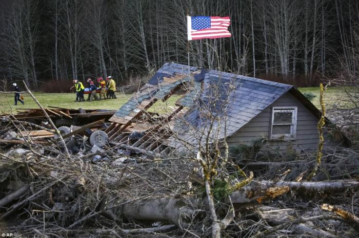 Here rescue workers are seen removing a body from the wreckage of homes destroyed by a mudslide near