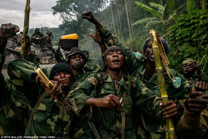 Government soldiers celebrate as they approach a militia stronghold in an effort to defeat the infam