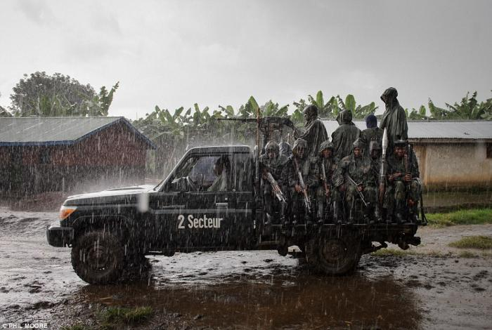 Government forces depart a position amid a torrential downpour.