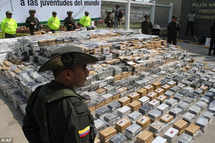 Police officers stand guard over seized packages of cocaine displayed for the press at a police base