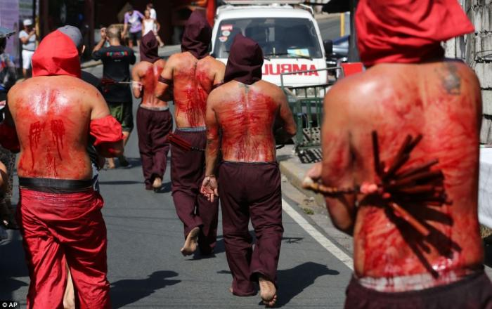 Hooded penitents in the Philippines flagellate themselves as part of the Maundy Thursday rituals to