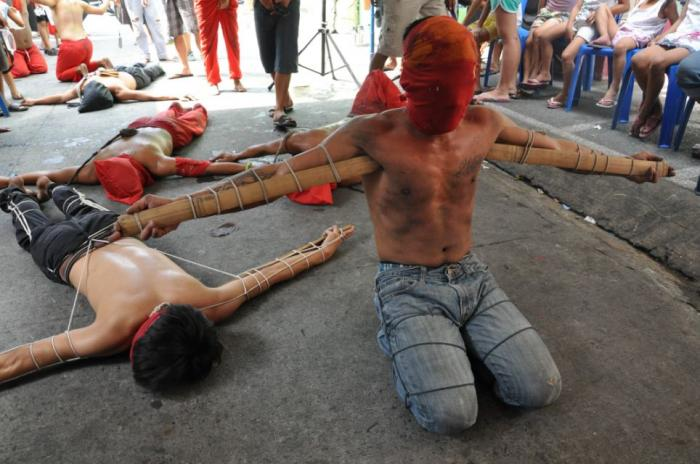 Devotees with wooden stakes tied to their arms pray during a painful ritual as part of the observanc