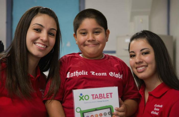 Michele and Lucia present a tablet to a happy student.