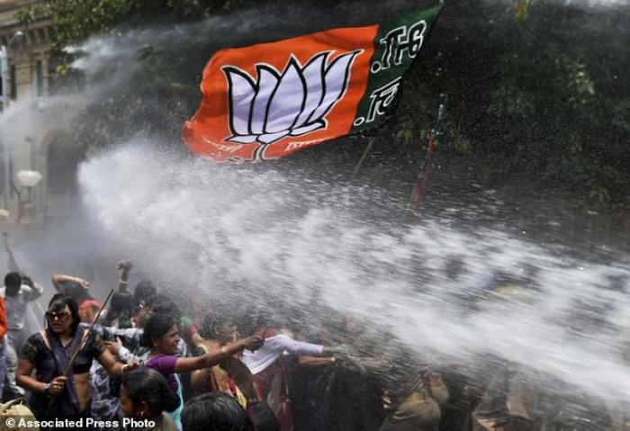 Women activists of Bharatiya Janata Party, flag seen top, face police water cannons as they demonstr