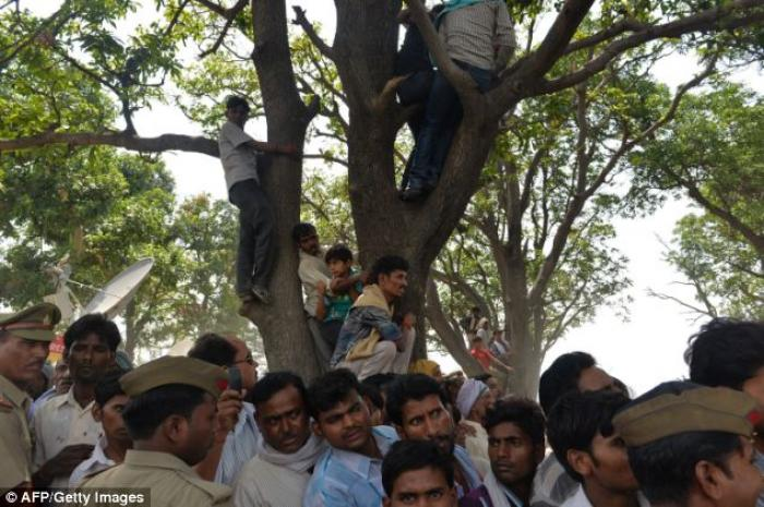 Villagers hold a protest beside the tree where they discovered the dead girls