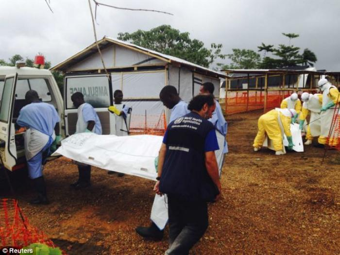Volunteers carry bodies to a van in a medical center for Ebola patients in Kailahun, Sierra Leone.