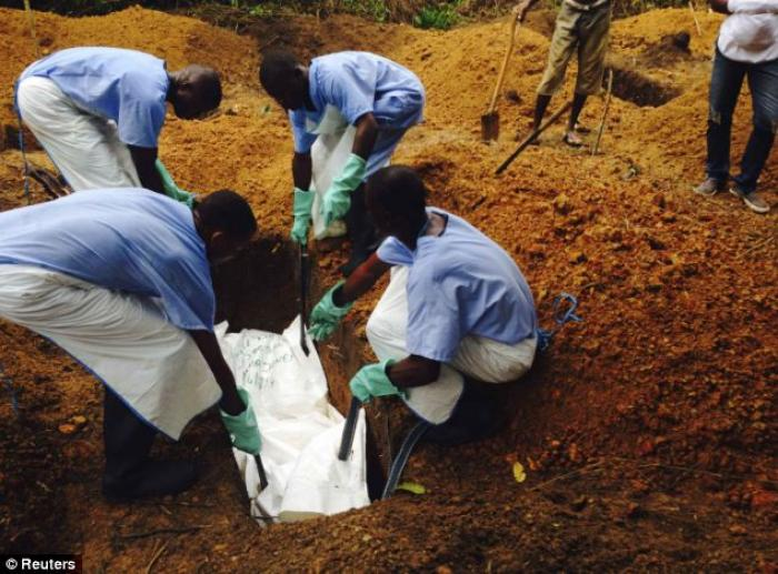 Volunteers lower a corpse into the ground in Kailiahun, Sierra Leone. The body has been prepared wit