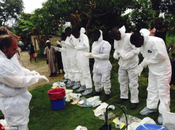 Volunteers get changed into white bodysuits as they prepare remove the bodies of people who were sus