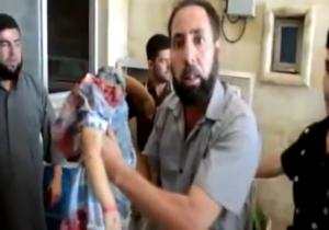 A distraught father in Syria holds the lifeless body of his decapitated daughter, executed by milita