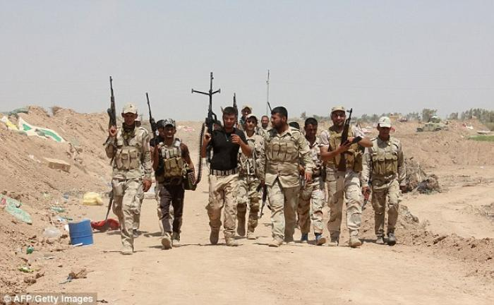 Iraqi volunteers who joined government forces to fight against Isis hold a position at a checkpoint