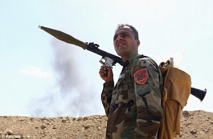 A member of the Kurdish peshmerga takes his position holding a rocket-propelled grenade launcher dur