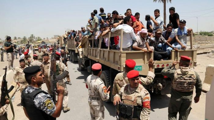 Iraqi men board military trucks to join the Iraqi army at the main recruiting center in Baghdad, Ira
