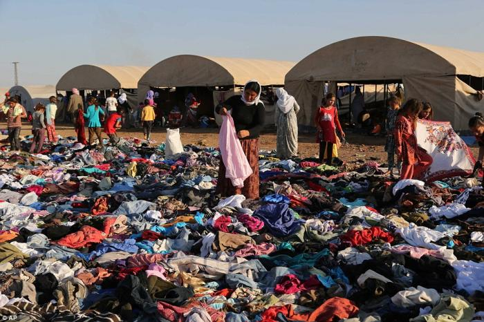 Displaced Iraqis from the Yazidi community look for clothes to wear among items provided by a charit