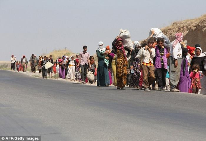 Displaced Iraqi families from the Yazidi community in Sanjir cross the Iraqi-Syrian border at Fishkh