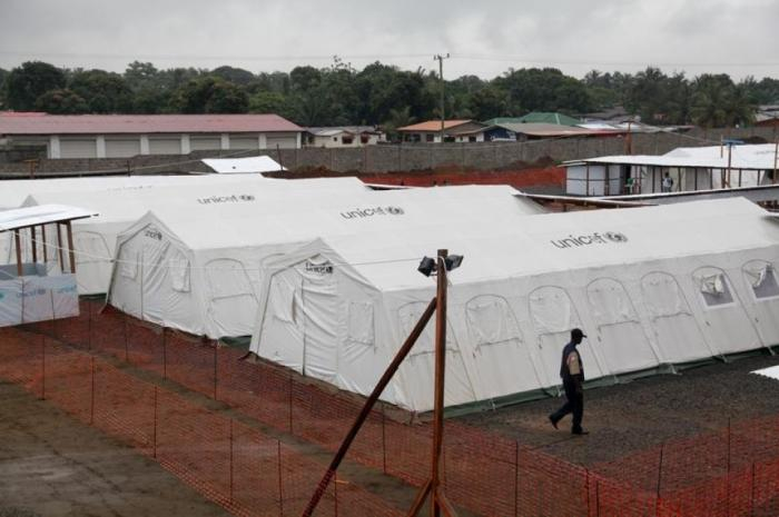 A worker walks past newly erected quarantine tents at the expanded ELWA Ebola Treatment Centre on th