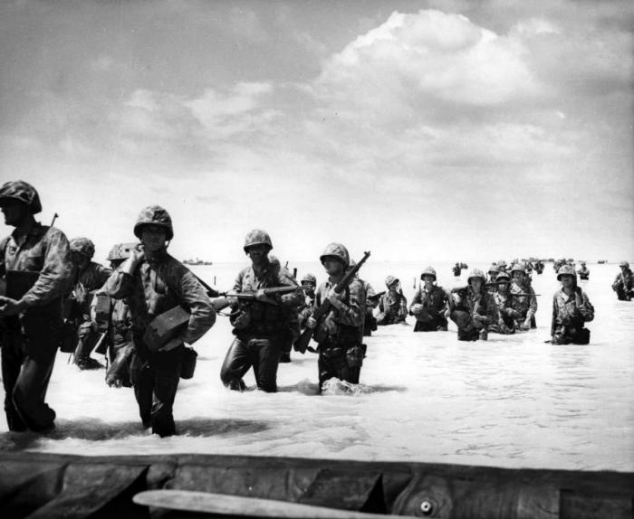 Marines wade ashore through the lagoon after their transport ran aground on the exposed coral.