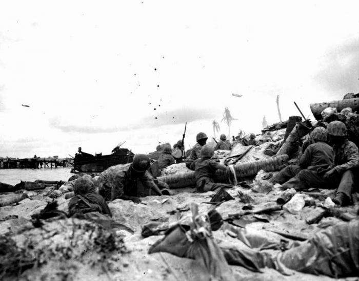 Marines on the beach, taking cover from Japanese fire behind the seawall.