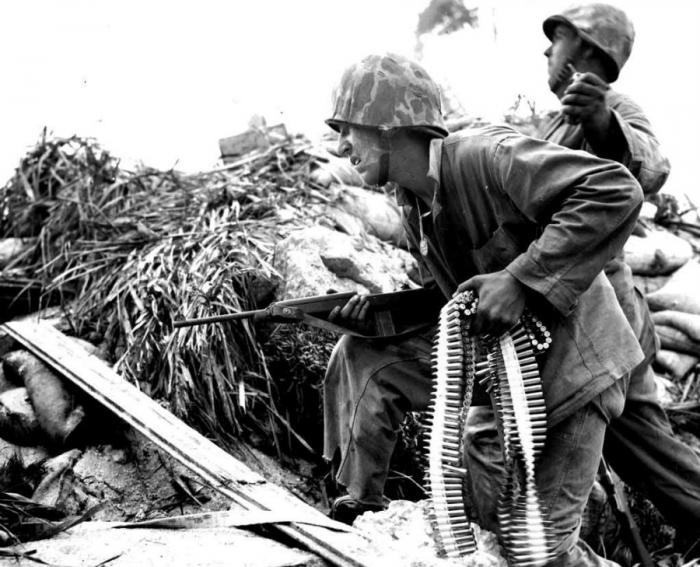 A Marine with a belt of ammunition for a machine gun, prepares to advance.