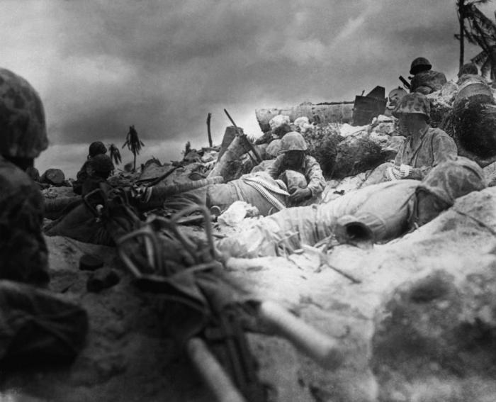 Marines on the beach under fire from Japanese defensive positions.