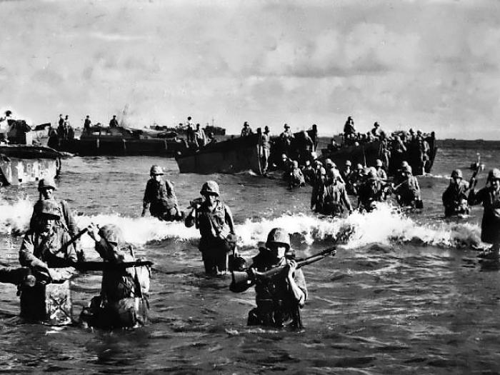 Marines wading ashore through the lagoon.